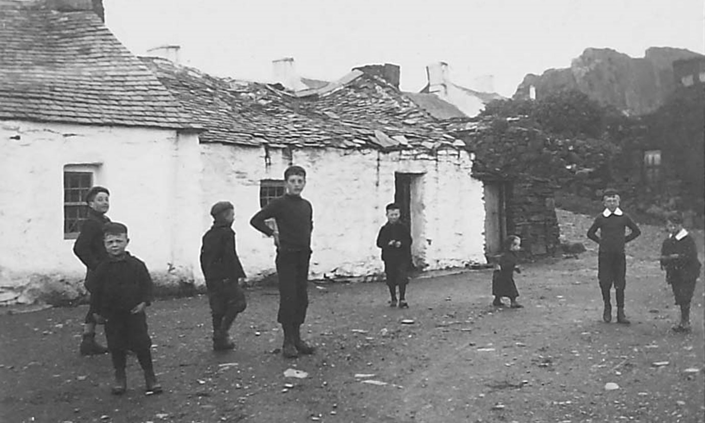 A group of 8 infant and pre-teen children from the 1890s stand in front of cottages that appear to be in disrepair.