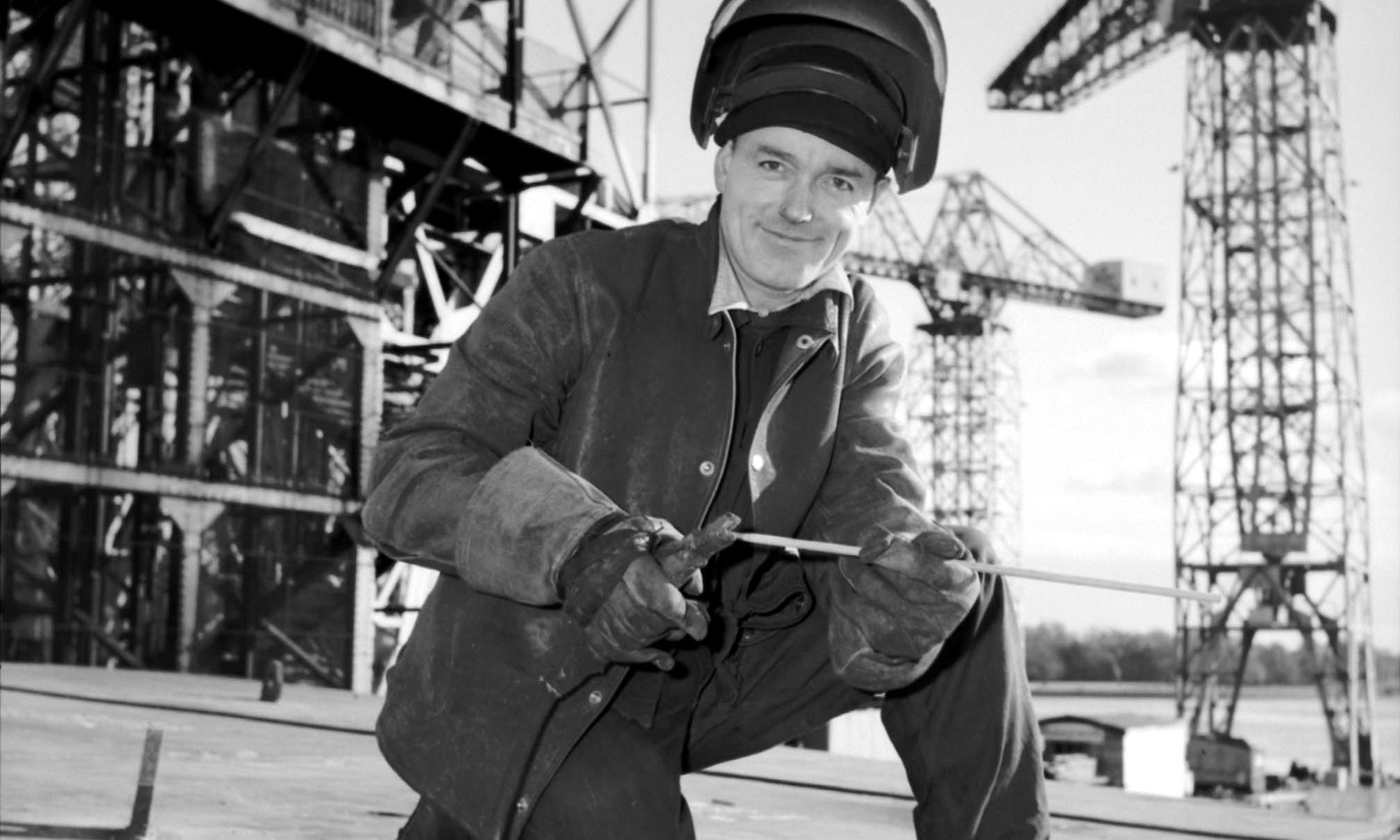 A shipyard welder, kneeling and wearing safety equipment and holding tools. In the background are cranes and scaffolding.