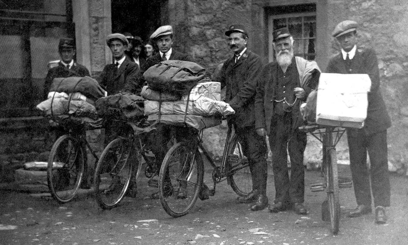 6 men are standing in smart clothes holding either sacks of post or bikes with mailbags and parcels.