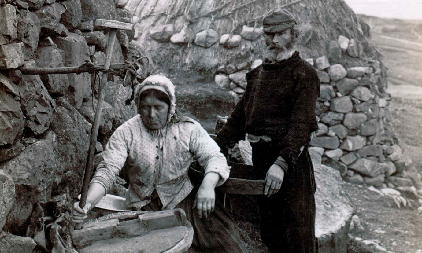 A woman and man working outside a stone cottage on the island of St. Kilda in the 1880s.